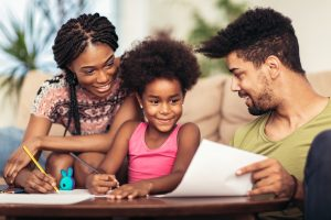 Mom and dad drawing with their daughter. African american family spending time together at home.