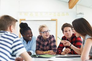 Group Of Teenage Students Collaborating On Project In Classroom
