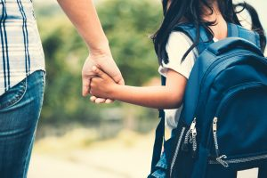 Girl with backpack holding her mother hand and going to school
