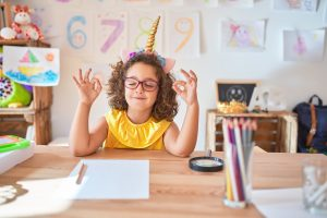 Beautiful toddler wearing glasses and unicorn diadem sitting on desk at kindergarten relax and smiling with eyes closed doing meditation gesture with fingers. Yoga concept.