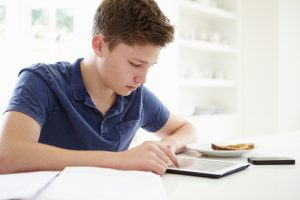 Teenage Boy Studying Using Digital Tablet At Home