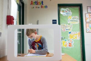 A second-grade boy paints a picture during art class. <br /> <strong>