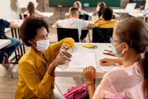 African American teacher and schoolgirl wearing protective face masks while discussing about test results on a class at the school.