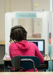 A fifth-grade student works on her laptop behind a personal protection shield at Wesley Elementary School. <br /> <strong> Photo by Allison Shelley for American Education: Images of Teachers and Students in Action </strong>
