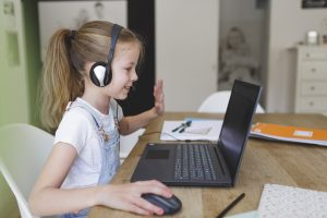 girl with headset is sitting in front of her laptop