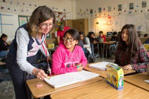 A teacher reviews a student's work in English class.