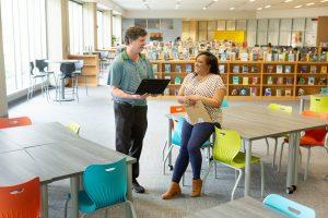 Two middle school teachers take a break in their school's library.