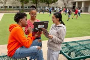 Three eighth-grade students work together on an assignment in a school courtyard.