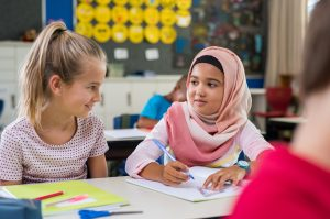 Young arab girl with hijab doing exercise with her bestfriend at international school. Asian muslim school girl sitting near her classmate during lesson. Multiethnic elementary students in classroom.
