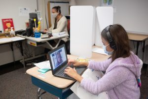 A fifth-grade student in school collaborates with a classmate learning from home.